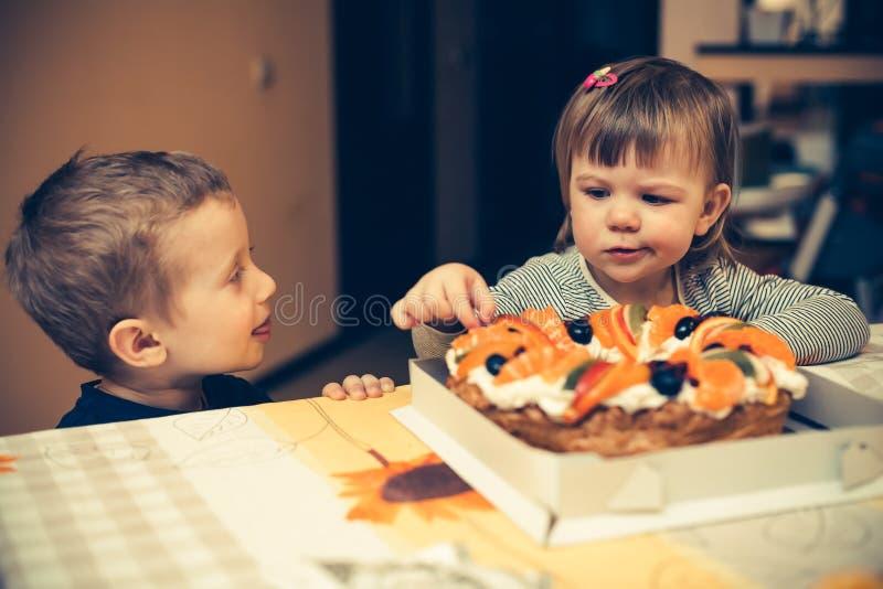 Niños que van a comer una torta imagen de archivo libre de regalías