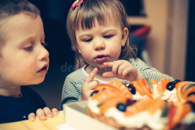 Niños que van a comer una torta fotografía de archivo