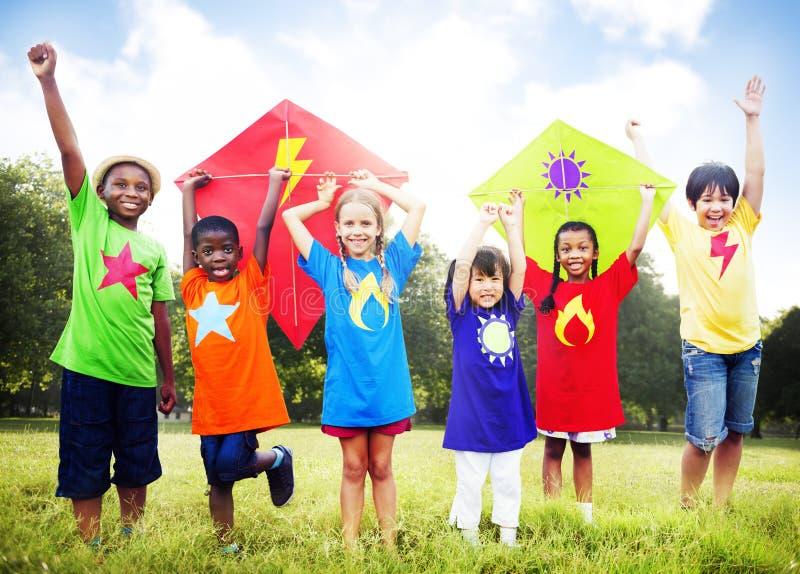 Niños que vuelan concepto juguetón de la amistad de la cometa imágenes de archivo libres de regalías
