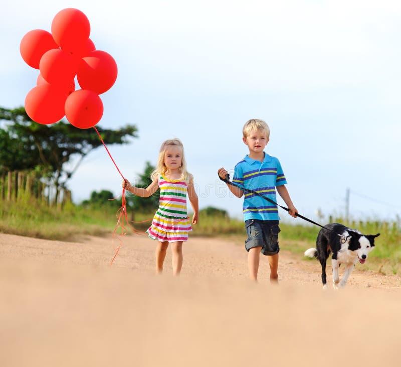 Niños rubios lindos que juegan al aire libre fotos de archivo libres de regalías