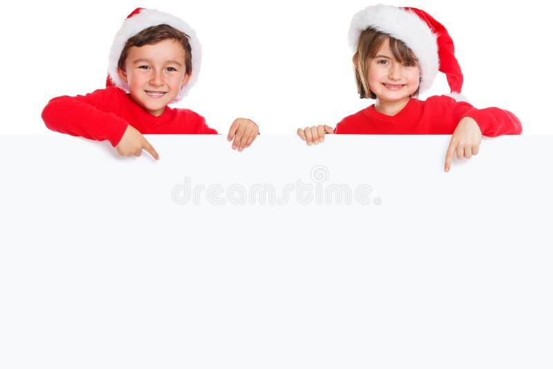 Niños Santa Claus de los niños de la Navidad que señala la bandera vacía feliz aislada en el espacio blanco de la copia del copys foto de archivo