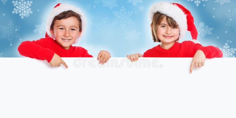 Niños Santa Claus de los niños de la Navidad que señala el espacio vacío feliz de la copia del copyspace de la bandera fotos de archivo libres de regalías