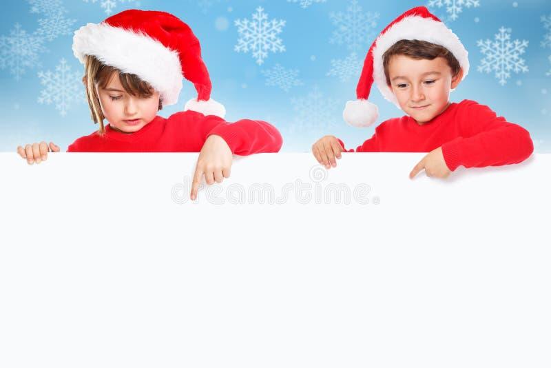 Niños Santa Claus de los niños de la Navidad que señala la nieve vacía c de la bandera imagen de archivo libre de regalías