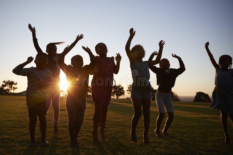 Niños silueteados de la escuela que saltan al aire libre en la puesta del sol foto de archivo