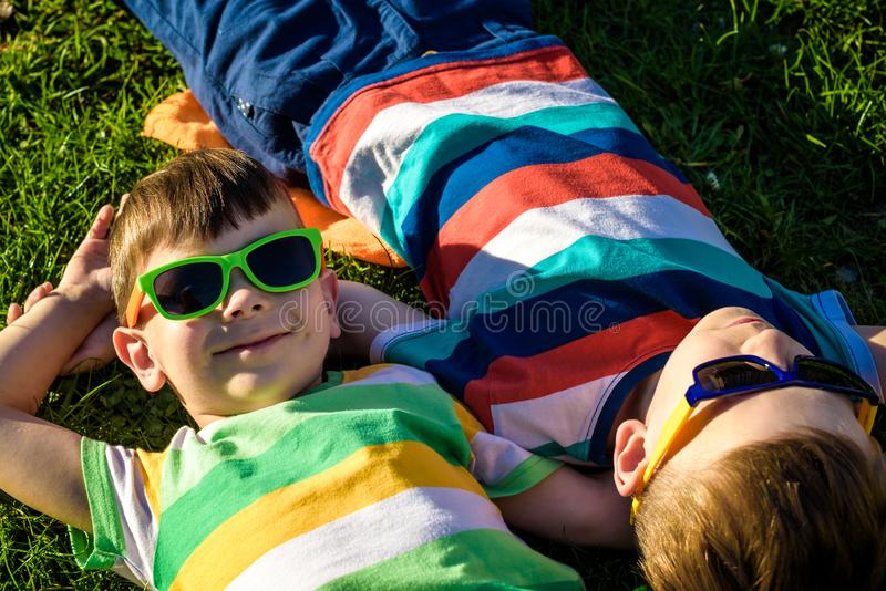 Niños sonrientes alegres felices, poniendo en una hierba, el llevar cantado fotografía de archivo
