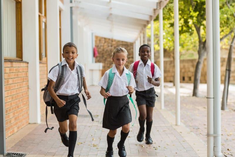 Niños sonrientes de la escuela que corren en pasillo fotografía de archivo libre de regalías
