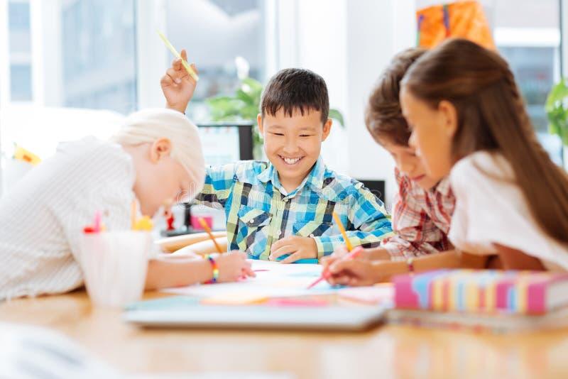 Niños sonrientes emocionados que unen en la escuela foto de archivo libre de regalías