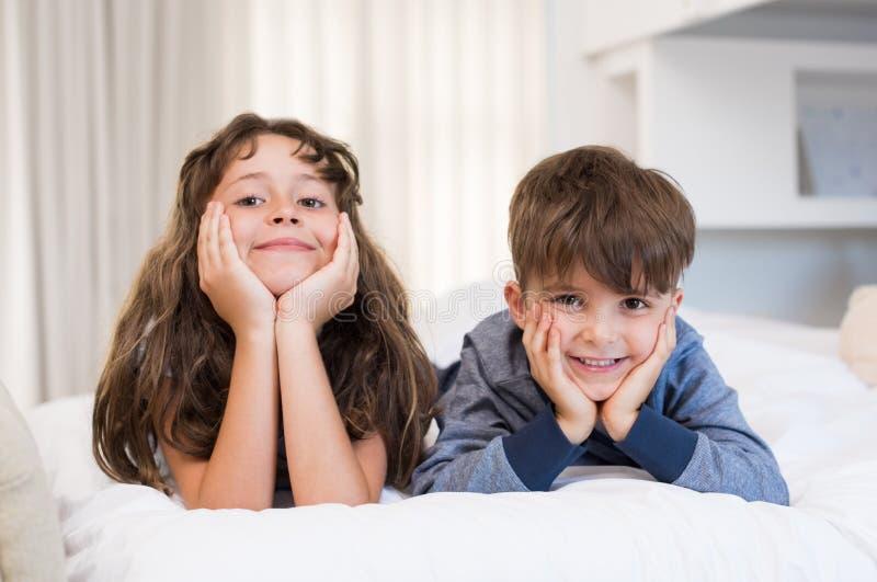 Niños sonrientes en cama imágenes de archivo libres de regalías