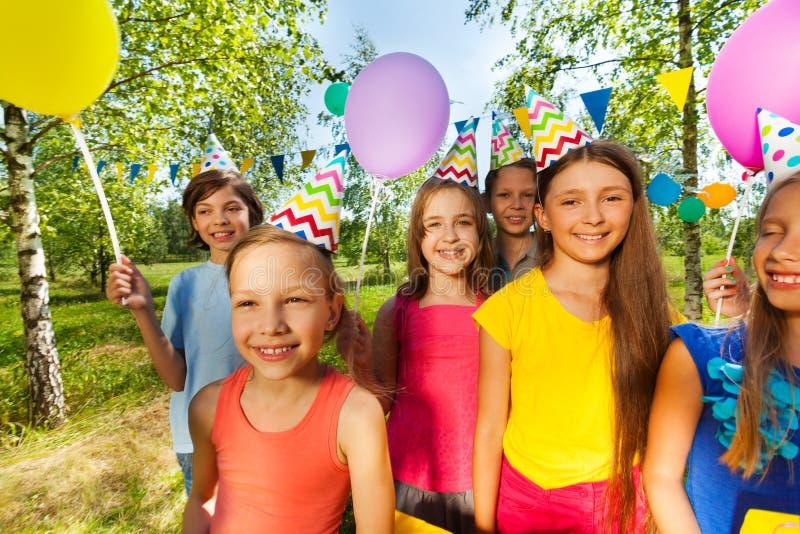 Niños sonrientes en sombreros del partido que celebran cumpleaños imágenes de archivo libres de regalías