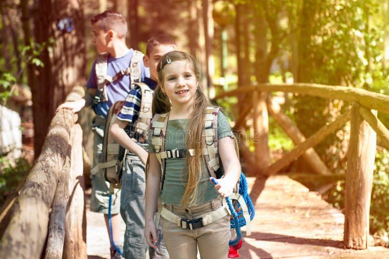 Niños sonrientes felices que cruzan un puente de madera en el bosque imágenes de archivo libres de regalías