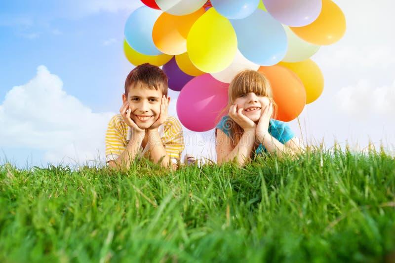 Niños sonrientes felices que mienten en la hierba verde con el colorfull b imagen de archivo libre de regalías