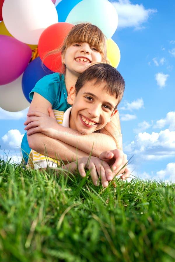 Niños sonrientes felices que mienten en la hierba verde con el colorfull b imágenes de archivo libres de regalías