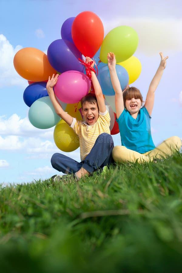 Niños sonrientes felices que mienten en la hierba verde con el colorfull b fotos de archivo