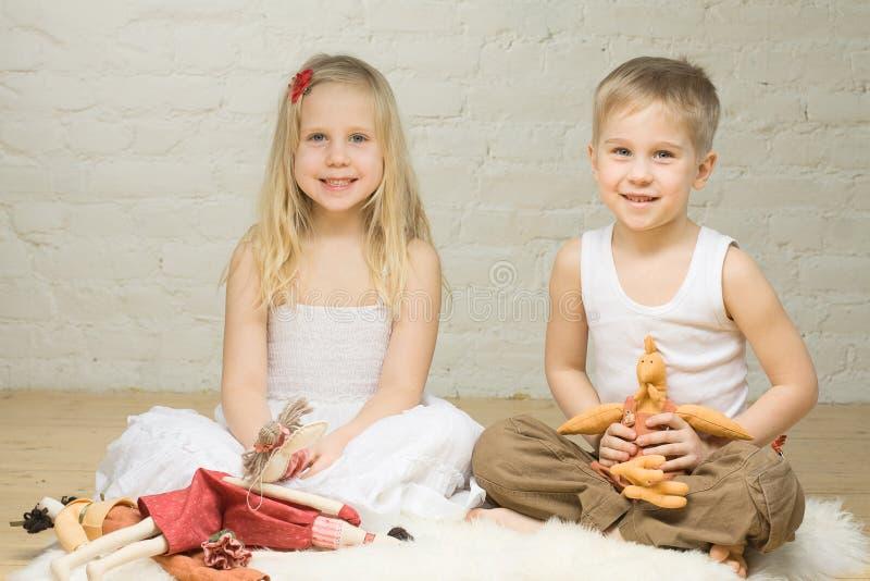 Niños sonrientes que juegan con los animales rellenos fotos de archivo