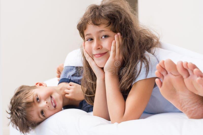 Niños sonrientes que mienten en cama foto de archivo libre de regalías