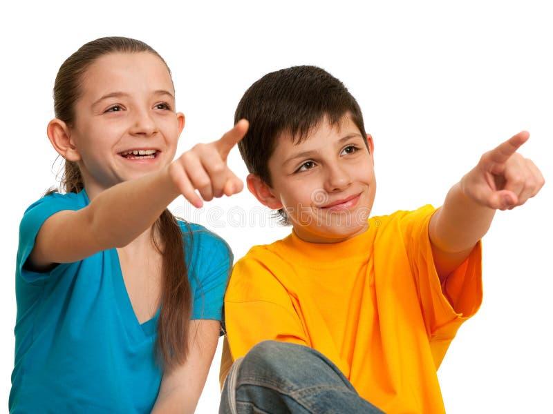 Niños sonrientes que señalan adelante imagen de archivo