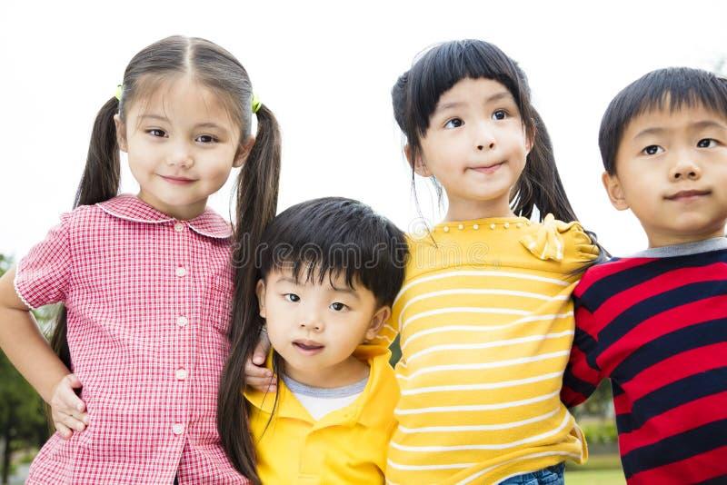 Niños sonrientes que se colocan afuera junto fotografía de archivo libre de regalías