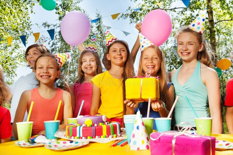 Niños sonrientes que se colocan al lado de la torta de cumpleaños imagenes de archivo