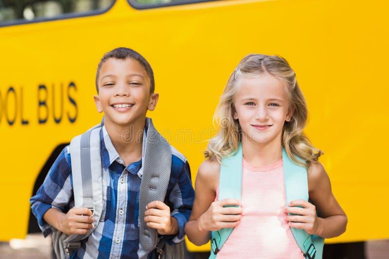 Niños sonrientes que se colocan delante del autobús escolar imagenes de archivo
