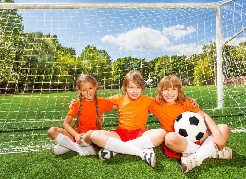Niños sonrientes que se sientan en hierba con fútbol imagenes de archivo