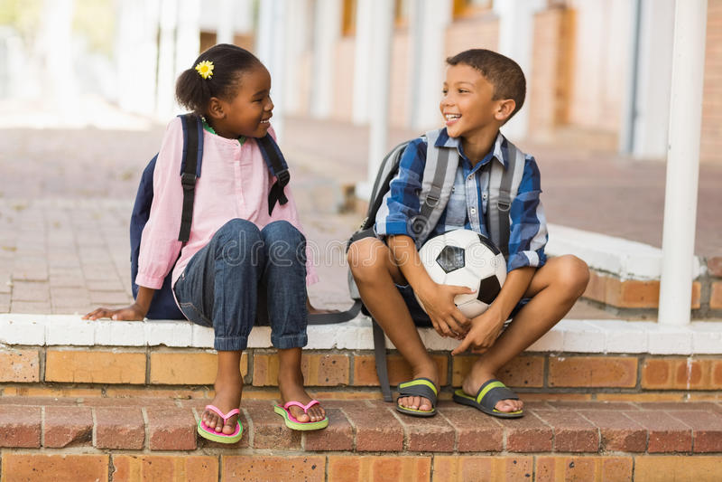 Niños sonrientes que se sientan en las escaleras en la escuela fotografía de archivo libre de regalías