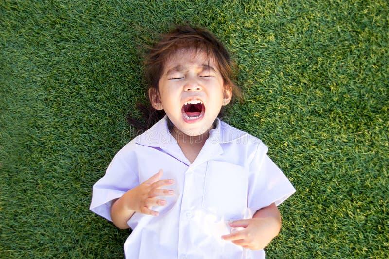 niños tailandeses asiáticos que lloran en hierba verde imagenes de archivo