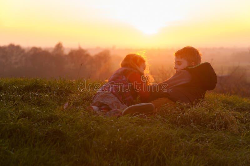 Niños teniendo en cuenta una puesta del sol fotos de archivo libres de regalías