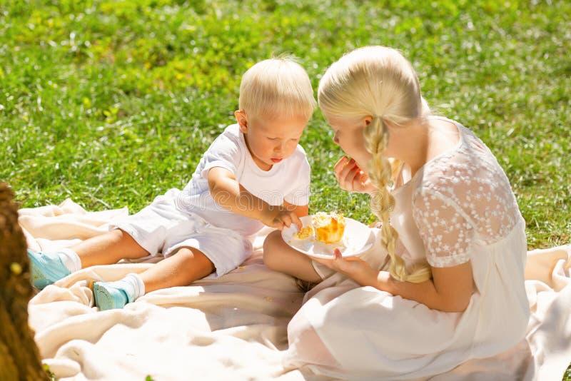 Niños tranquilos que comen los dulces en el parque fotografía de archivo