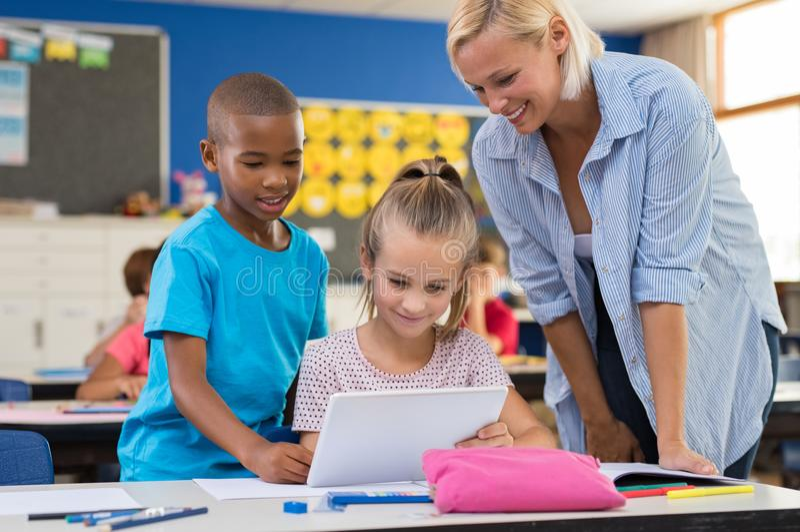 Niños usando la tableta digital en sala de clase imagen de archivo libre de regalías