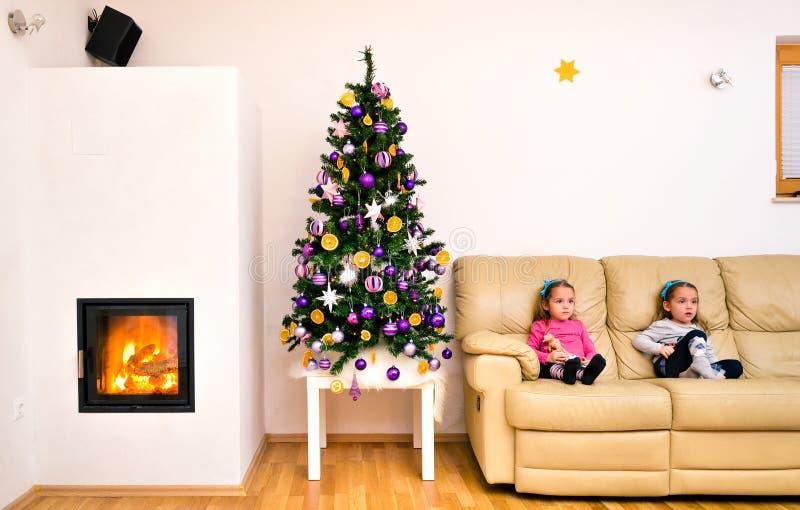 Niños y árbol de navidad en el apartamento de lujo moderno con el fuego fotografía de archivo