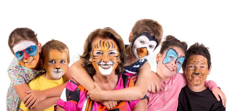 Niños y abuelita con la cara-pintura animal fotos de archivo