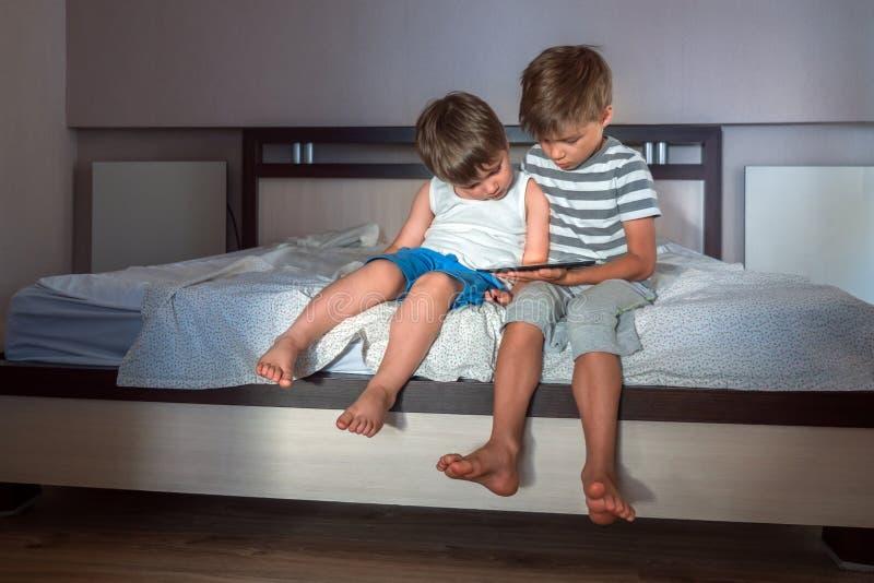 Niños y artilugios Dos muchachos con la tableta en las rodillas Concepto el enseñar casero Fondo de la preescolar Hogar fotos de archivo