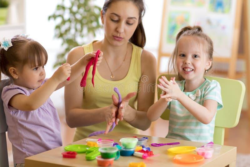 Niños y juguete colorido de la arcilla del juego de la madre imagenes de archivo