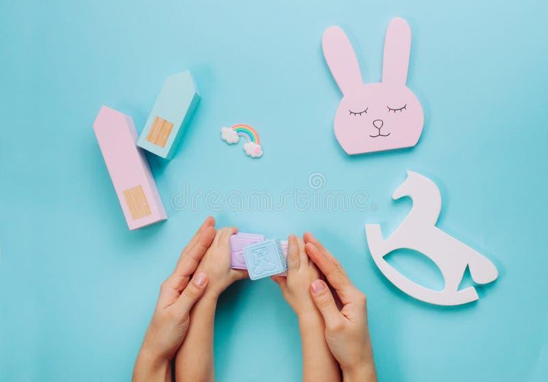 Niños y las manos de la madre que juegan con los juguetes en fondo azul fotografía de archivo