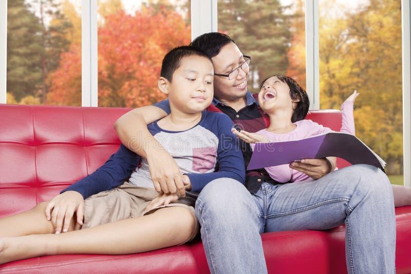 Niños y libro de lectura del padre en el sofá imágenes de archivo libres de regalías