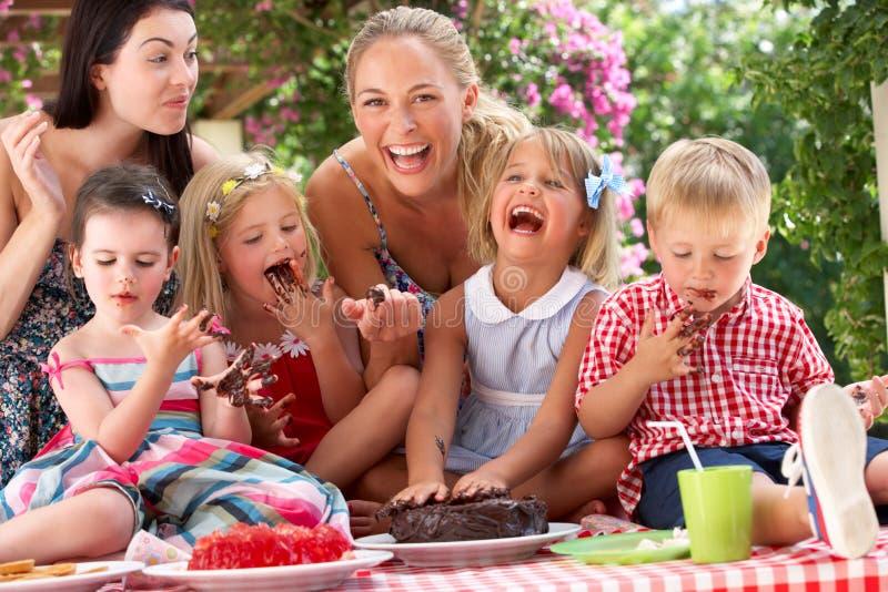 Niños y madres que comen la torta en Outd imagen de archivo libre de regalías