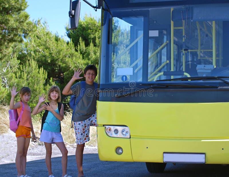 Niños y omnibus amarillo fotografía de archivo