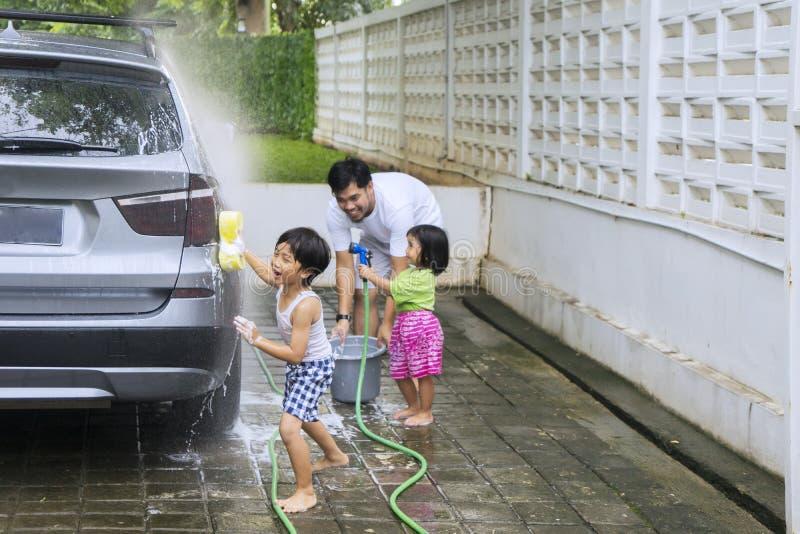 Niños y padre que lavan un coche foto de archivo