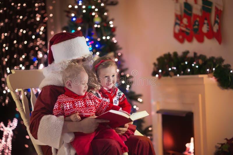 Niños y Papá Noel en el lugar del fuego el Nochebuena foto de archivo