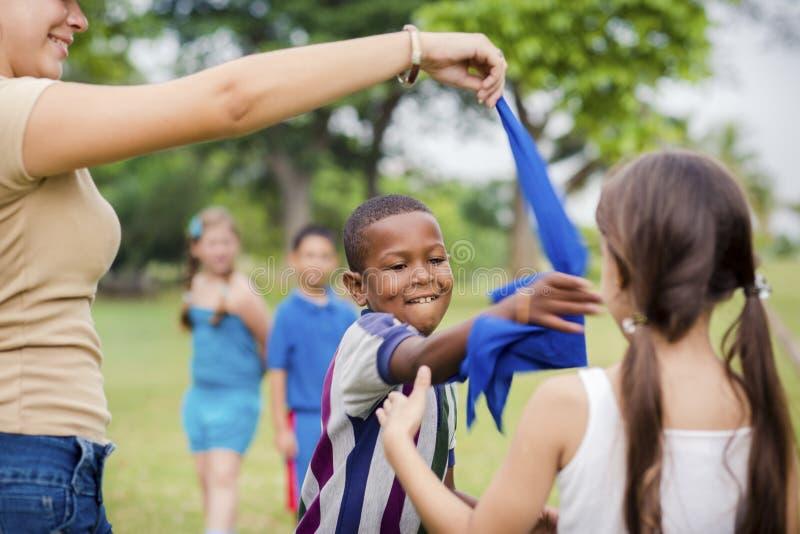 Niños y profesor que juegan a juegos en parque de la ciudad foto de archivo