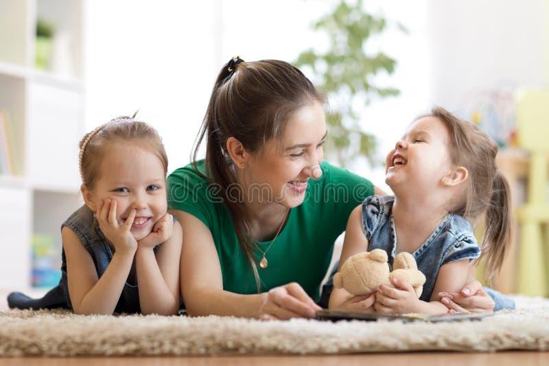 Niños y su madre que leen un libro en piso en casa imagenes de archivo