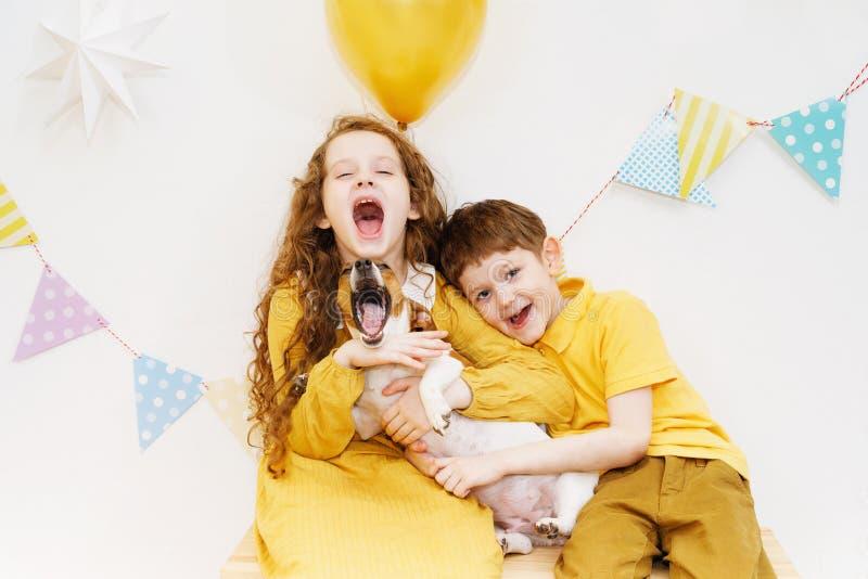 Niños y su perro abrazados y que cantan una canción para su nacimiento fotografía de archivo