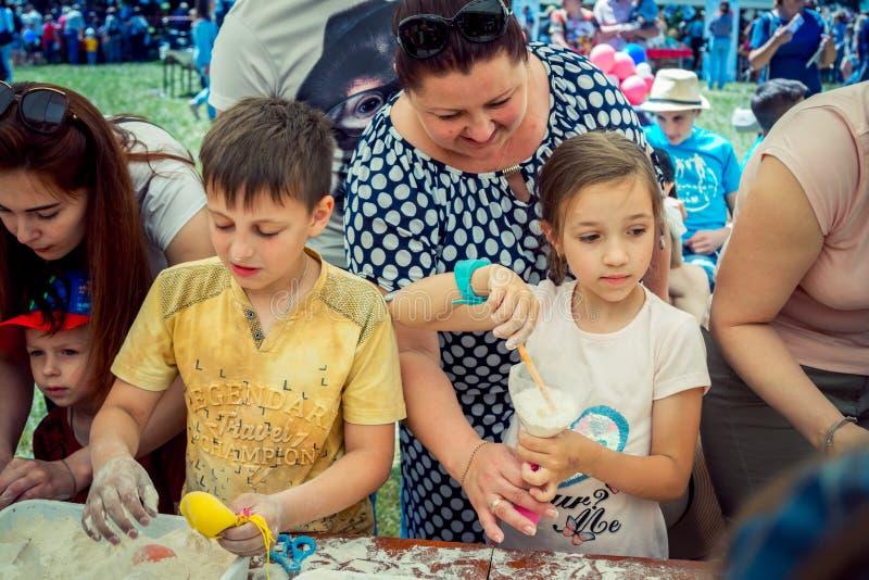 Niños y sus padres que participan en el taller antiesfuerzo de la creación del juguete imagen de archivo libre de regalías