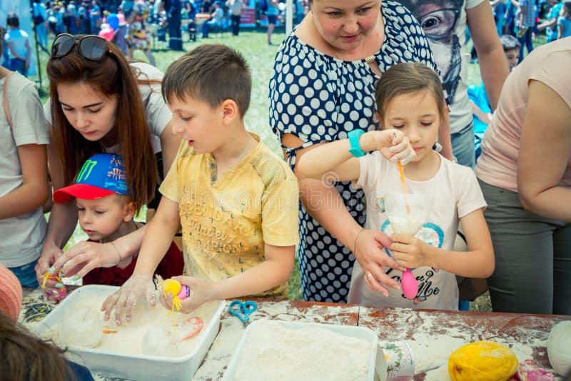 Niños y sus padres que participan en el taller antiesfuerzo de la creación del juguete foto de archivo libre de regalías