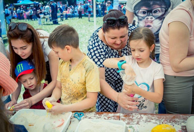 Niños y sus padres que participan en el taller antiesfuerzo de la creación del juguete foto de archivo