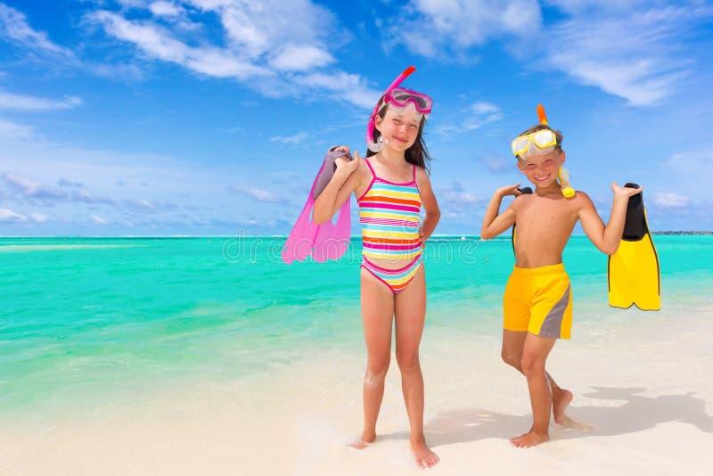 Niños y tubos respiradores en la playa imagen de archivo