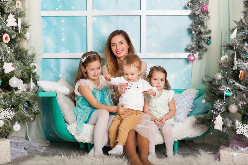 Niños y una madre joven en decoraciones de una Navidad imagenes de archivo