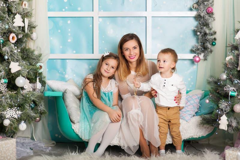 Niños y una madre joven en decoraciones de una Navidad imagen de archivo