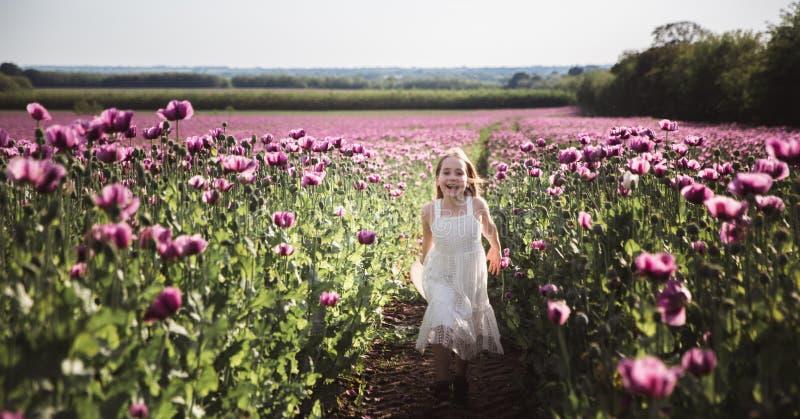 Ni?a adorable con el pelo largo en caminar solo del vestido blanco en el campo de Poppy Flowers de la lila imagen de archivo