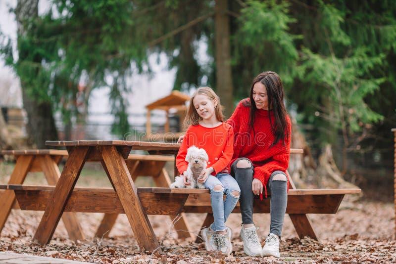 Ni?a adorable y madre joven con el perrito al aire libre imagenes de archivo